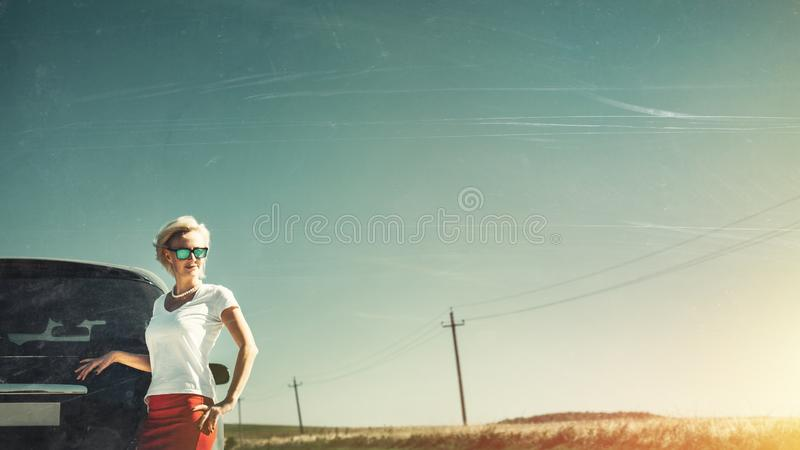 Middle aged independent woman enjoys road adventure. Toned Image with scratches and copy-space. Vacation, motivation, well-being,. Middle aged independent woman stock images