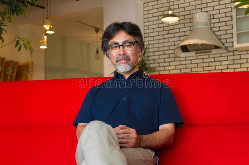 Japanese man relaxing on the sofa. Middle-aged Japanese man relaxing on red sofa in the living room stock photos