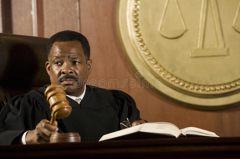 Middle Aged Judge Knocking Gavel. Serious middle aged judge knocking a gavel royalty free stock photo