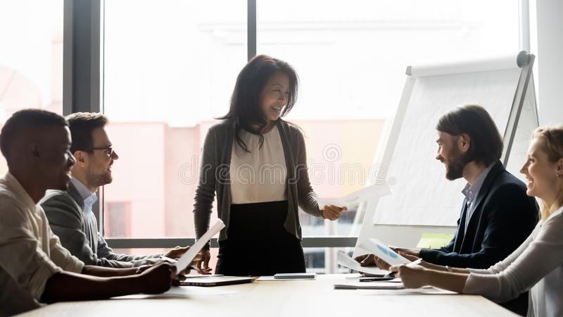 Middle aged korean female team leader discussing project with teammates. royalty free stock image