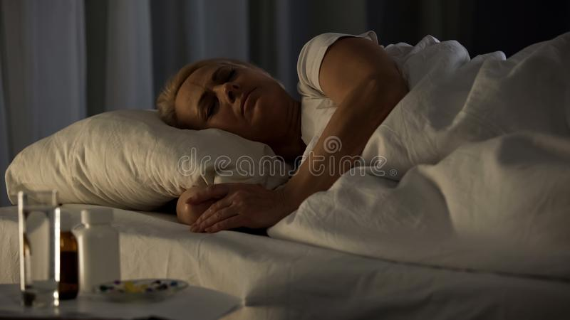 Middle-aged lady sleeping in bed, treatment pills table, health care, medicine. Stock photo stock photography