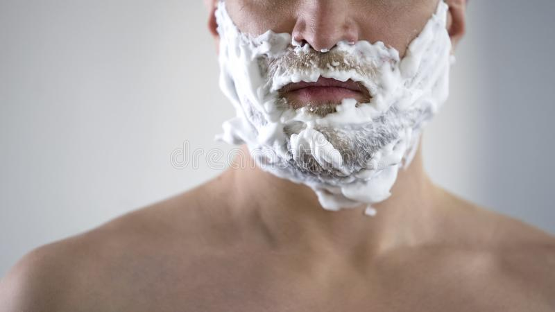 Middle-aged male disappointed and angry because of quality of new shaving foam. Stock photo royalty free stock photos