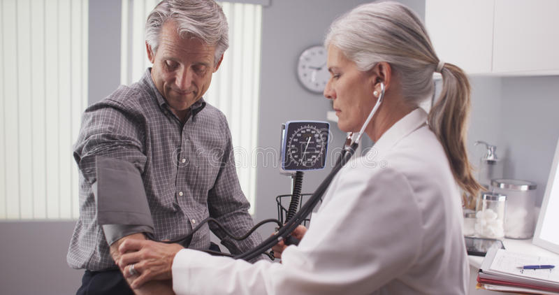 Middle-aged male patient having blood pressure checked royalty free stock images