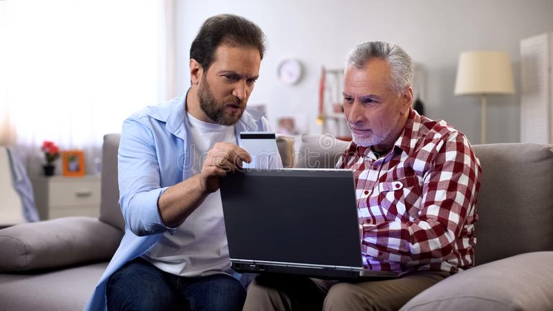 Middle aged male showing how to make payments through internet, online security. Stock photo stock photo