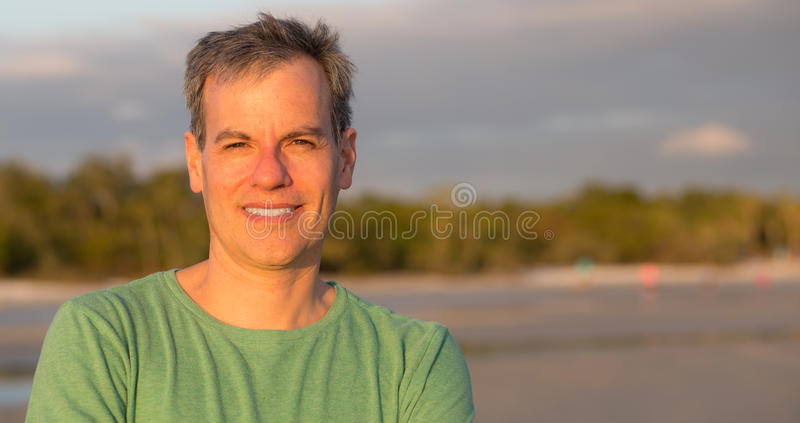 Middle aged man at the beach. Middle aged man on the beach at sunset with copy space royalty free stock images
