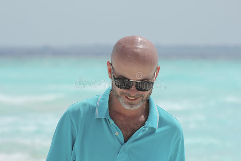 Middle-aged man on the beach in turquoise shirt royalty free stock photo