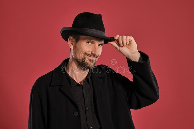 Middle-aged man with beard and mustache, wears black hat and jacket posing against a red background. Sincere emotions royalty free stock image