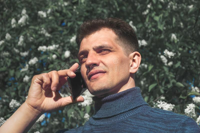 Middle-aged man in blue jumper holds his phone near ear, listens and looks away in summer park on sunny day stock image