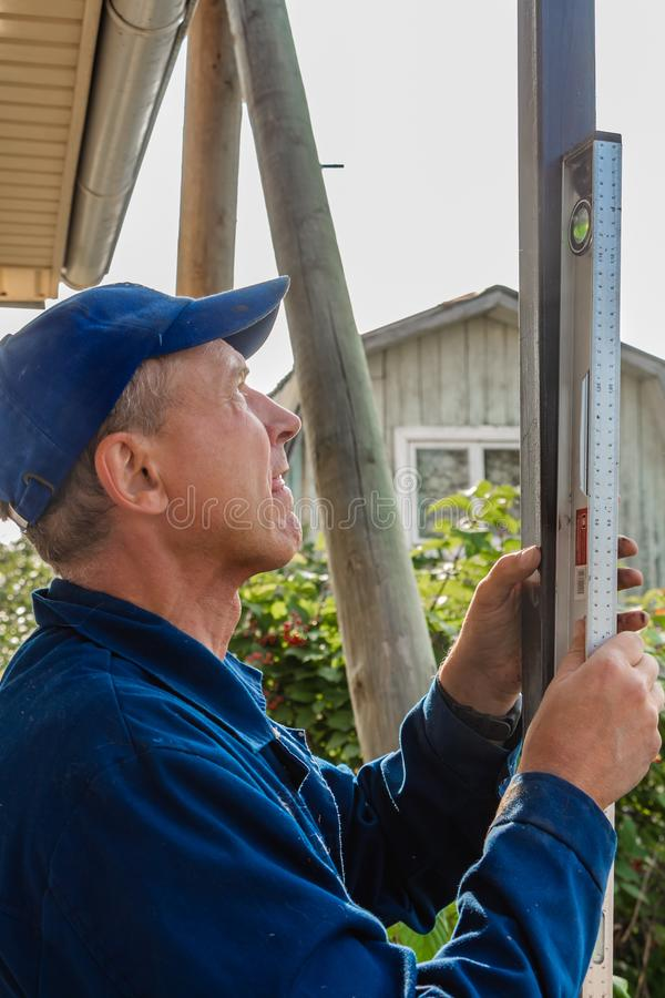 A middle-aged man builder in a blue jacket and blue cap places a black iron pillar on the level royalty free stock photos
