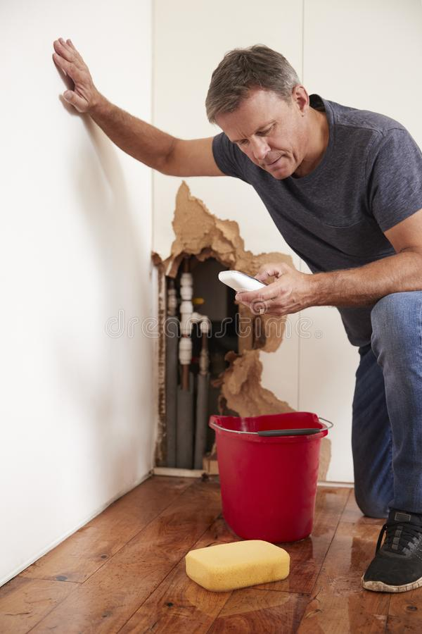 Middle aged man with a burst pipe dialling phone for help stock image