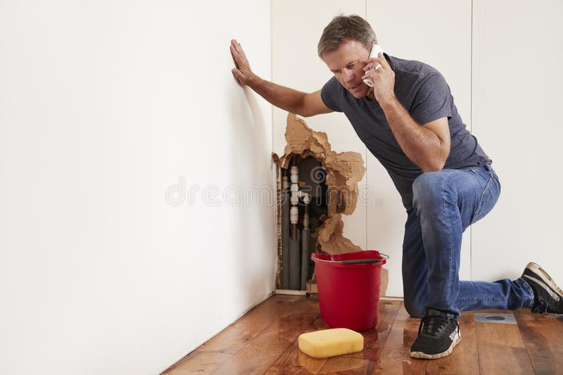 Middle aged man with a burst water pipe phoning for help royalty free stock photo