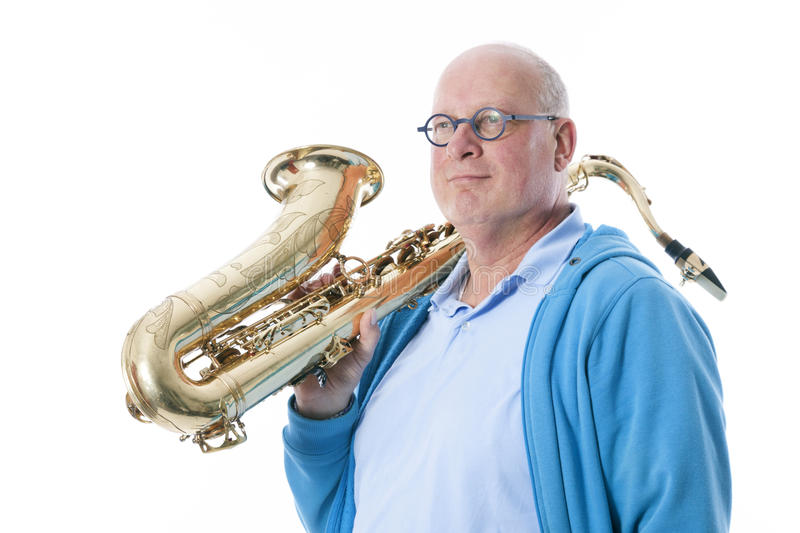 Middle aged man carries tenor saxophone on shoulder against whit. Middle aged man in blue plays the tenor saxophone against white studio background royalty free stock image