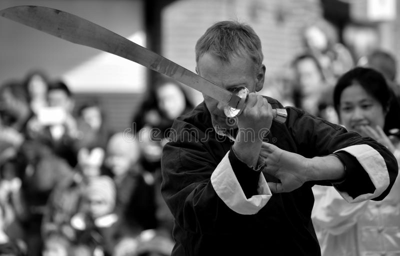 Middle aged man with Chinese sword. A picture of a middles aged man with Chinese sword at the Chinese New Year celebrations in Woking UK (2015 year of the sheep royalty free stock images