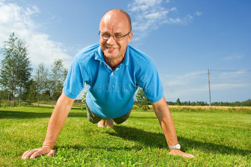 Middle-aged man doing push-ups. On grass stock photos