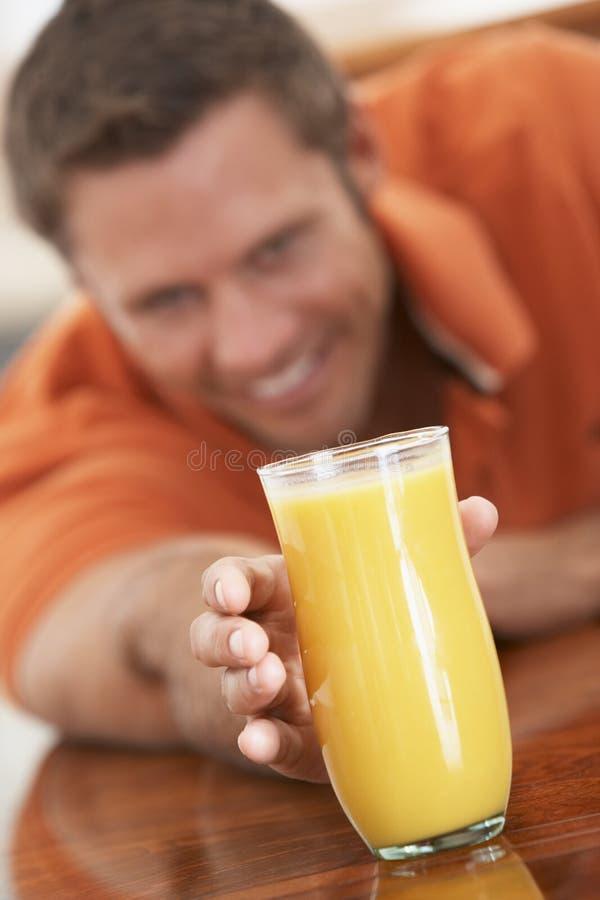 Middle Aged Man Drinking Fresh Orange Juice royalty free stock photography