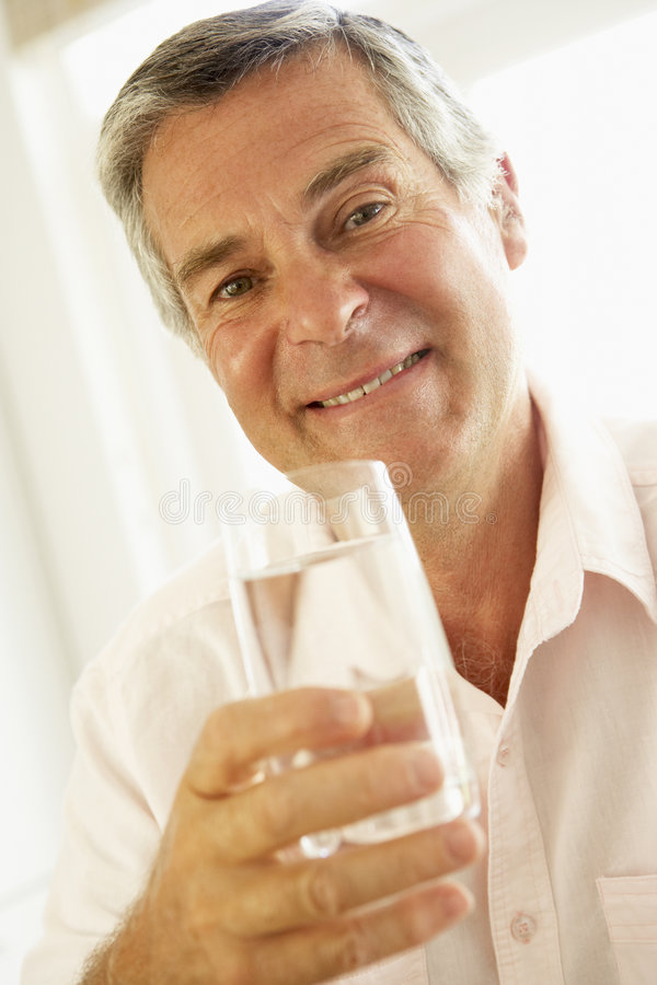 Middle Aged Man Drinking A Glass Of Water stock photo
