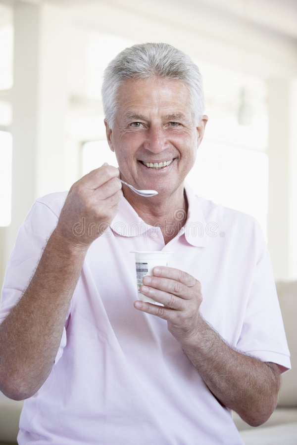 Download Middle Aged Man Eating Yogurt Stock Photo - Image of older, colour: 7875212