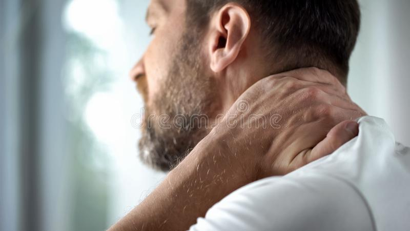 Middle-aged man feeling neck pain in morning, uncomfortable mattress, healthcare royalty free stock image