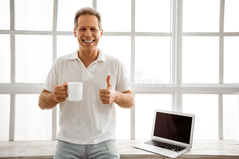 Middle aged man with gadget. Handsome middle aged man is holding a cup, showing Ok sign and smiling while sitting near the window at home, laptop in the stock photos