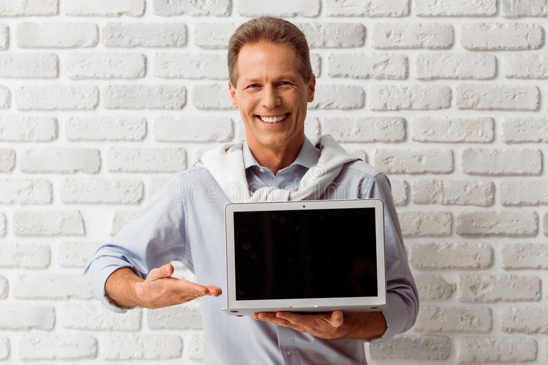 Middle aged man with gadget. Handsome middle aged man is showing a laptop, looking at camera and smiling, standing against white brick wall royalty free stock photo
