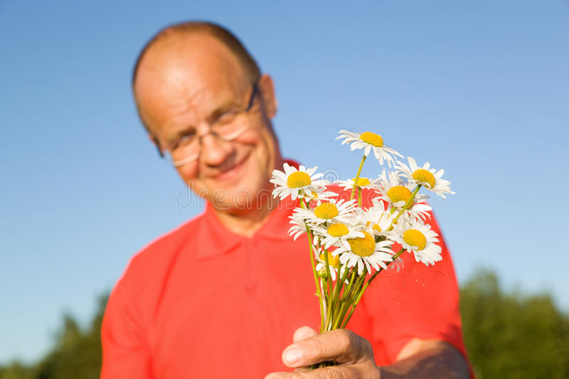 Middle-aged Man Giving Flowers Royalty Free Stock Photos