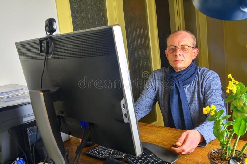 Middle aged man with glasses sitting at desk. Mature man using personal computer. Senior concept. Man working at home stock photo