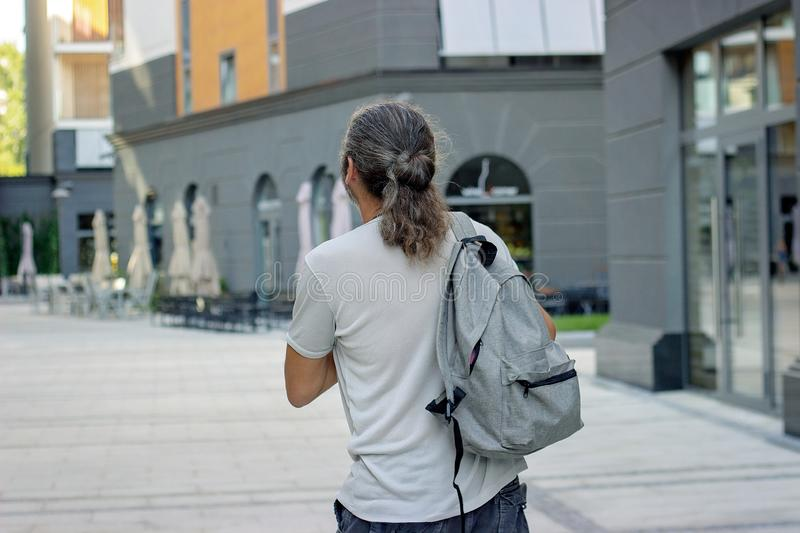 Middle aged man with gray backpack on the street; with copy space royalty free stock images