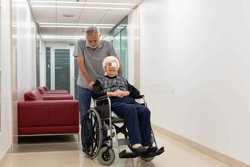 Middle aged man helping and taking to elderly 95 years old woman sitting in the wheelchair. stock photo