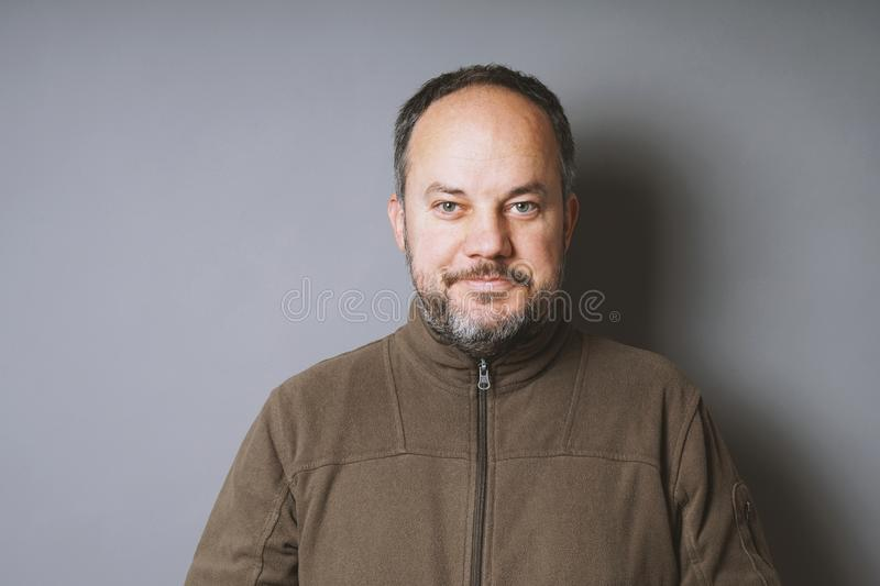 Middle aged man with short dark hair and graying beard smiling. Middle aged man in his 40s with short dark hair and graying beard smiling against gray wall with royalty free stock image