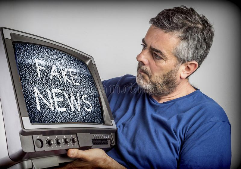 Middle-aged man holds a TV with fake news screen. Conceptual image stock photography