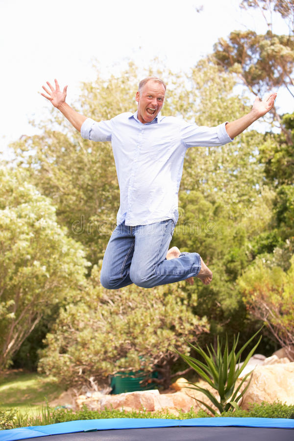 Middle Aged Man Jumping On Trampoline In Garden royalty free stock photo