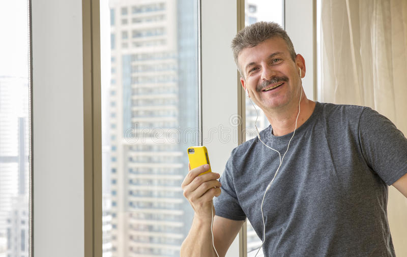Middle aged man listening music with head phones royalty free stock image