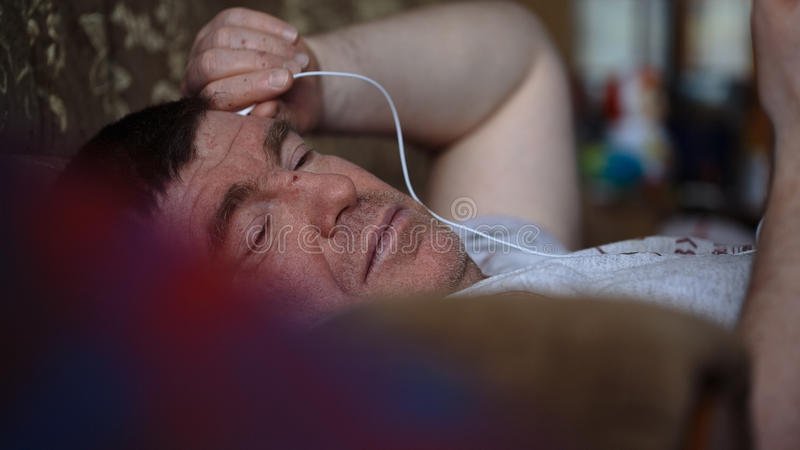 Middle-aged man lying on the couch and listen to music from your gadget. Closeup royalty free stock photography