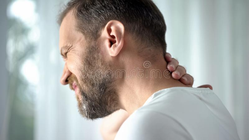 Middle aged man massaging neck, feeling discomfort, spinal problem, body care royalty free stock photos