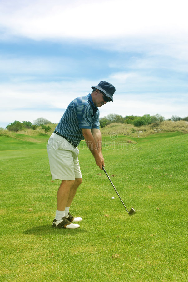 Middle aged man playing golf. stock image