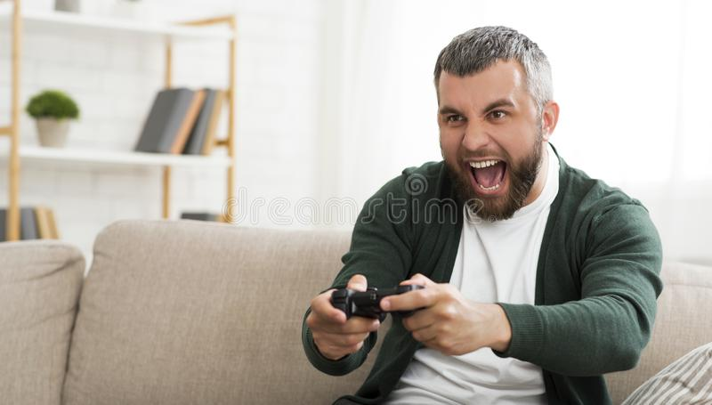 Middle-aged man playing video games at home. Emotional Middle-Aged Man Playing Video Game With Joystick At Home, copy space stock photography