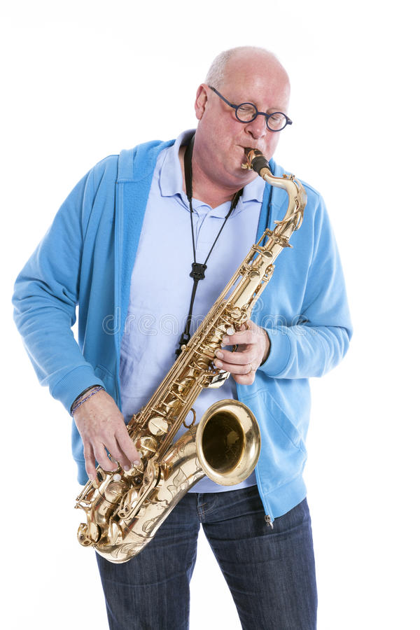 Middle aged man plays the tenor saxophone against white studio b. Middle aged man in blue plays the tenor saxophone against white studio background royalty free stock photography