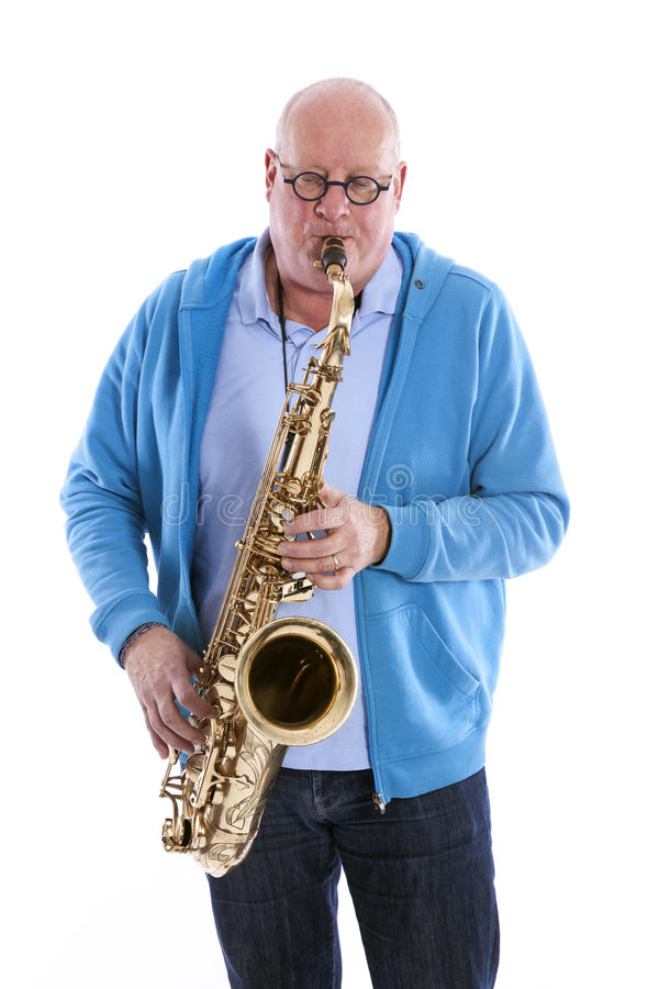 Middle aged man plays the tenor saxophone against white studio b. Middle aged man in blue plays the tenor saxophone against white studio background royalty free stock photos