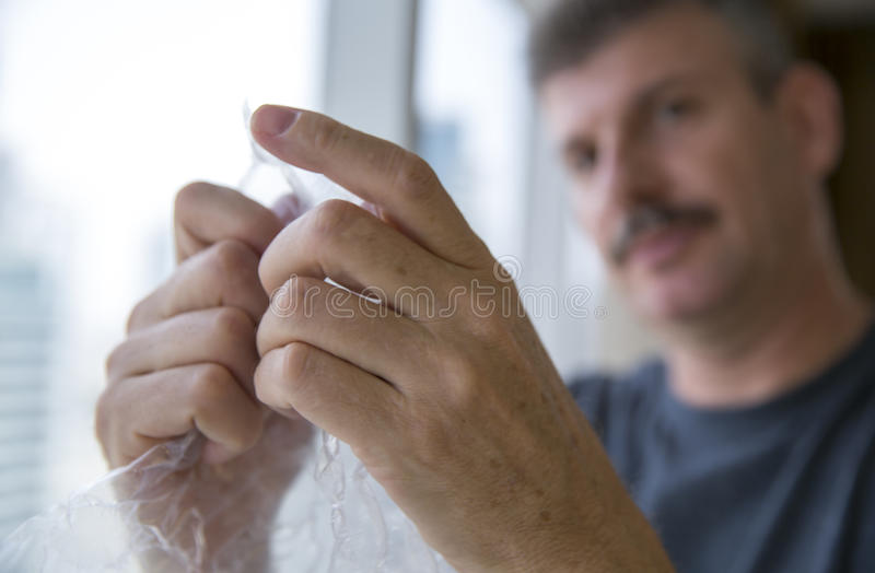 Middle aged man popping bubble wrap. Stressed middle aged man popping bubble wrap stock photos