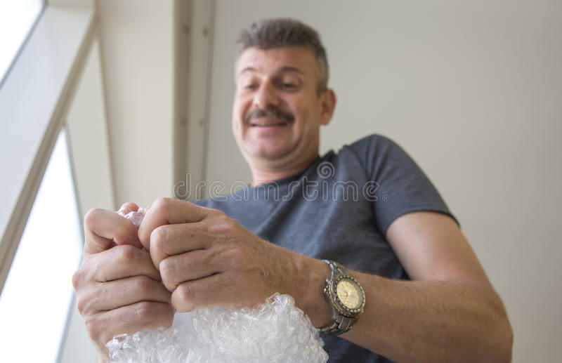 Middle aged man popping bubble wrap. Stressed middle aged man popping bubble wrap royalty free stock image