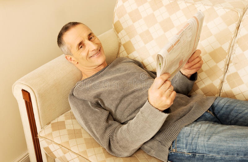 Middle-aged man reading newspaper at home stock images