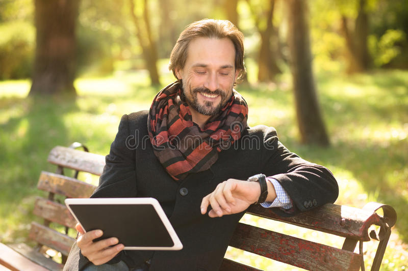 Middle-aged man resting on the bench outdoors stock images
