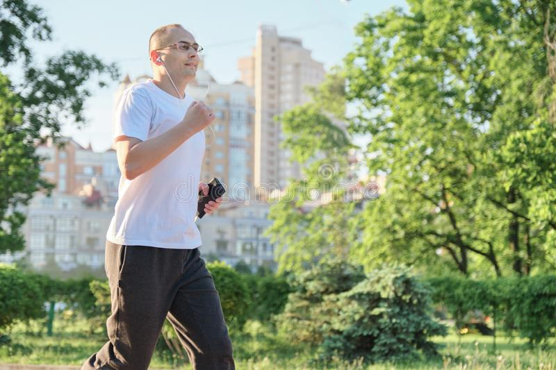 Middle-aged man running in the park, active healthy lifestyle stock images