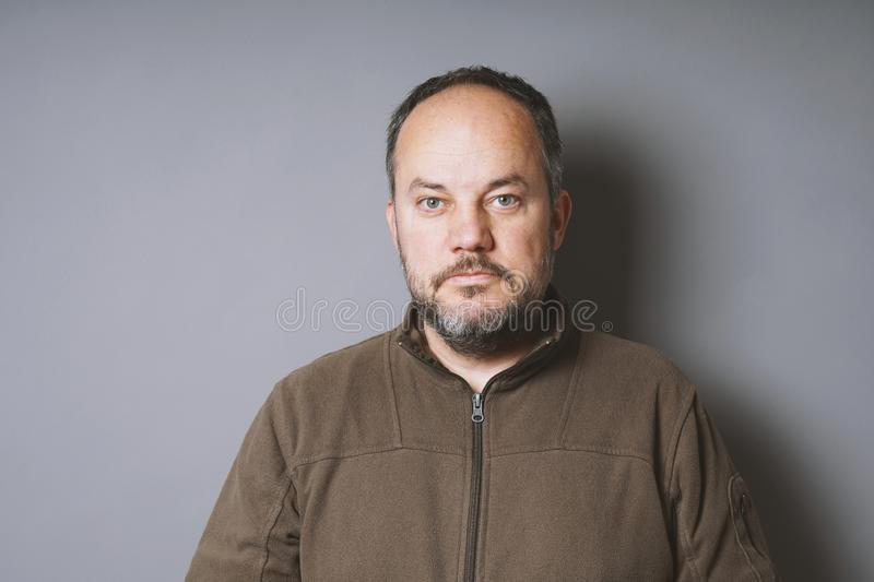 Middle aged man with short dark hair and graying beard. Middle aged man in his 40s with short dark hair and graying beard against gray wall with copy space royalty free stock photos