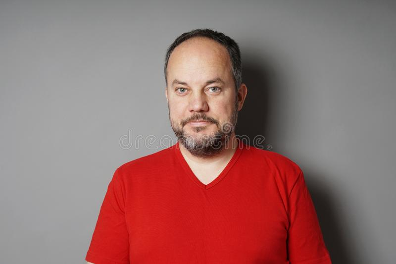Middle aged man with short dark hair and graying beard smirking. Middle aged man in his 40s wearing red t-shirt with short dark hair and graying beard smirking stock images