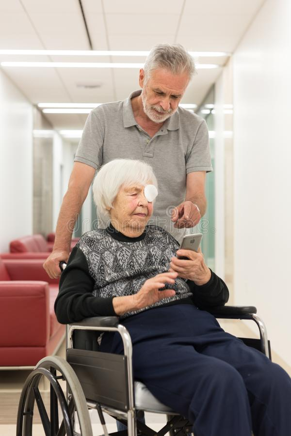 Middle aged man showing and helping elderly 95 years old woman sitting at the wheelchair how to use modern mobile phone. royalty free stock photos