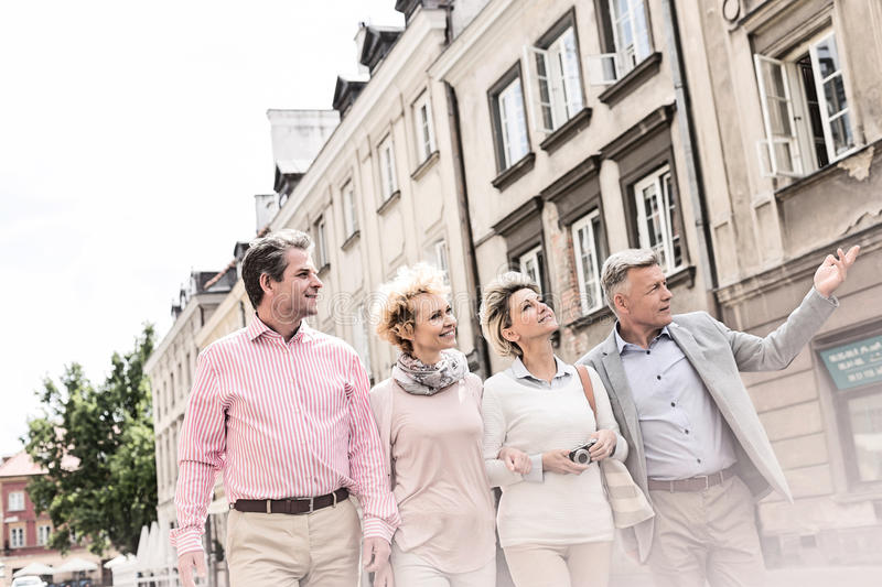 Middle-aged man showing something to friends while walking in city royalty free stock photos