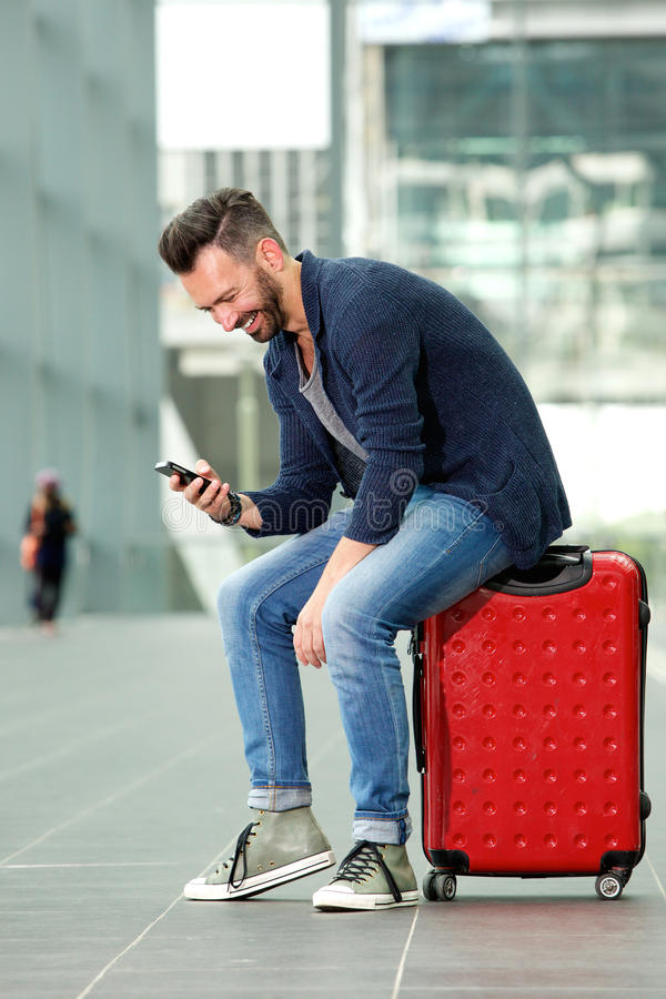 Middle aged man sitting on suitcase using mobile phone royalty free stock photography