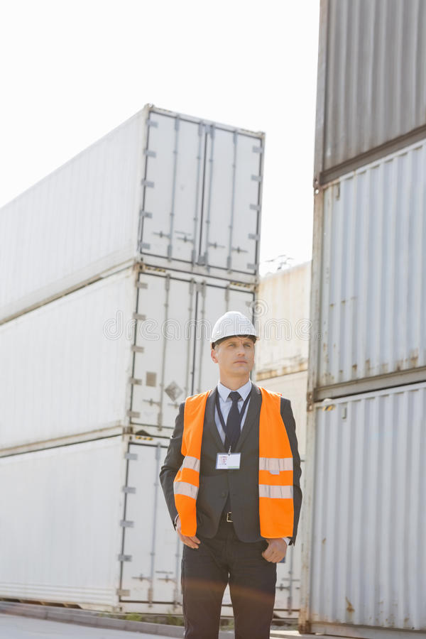 Middle-aged man standing against cargo containers in shipping yard royalty free stock photo