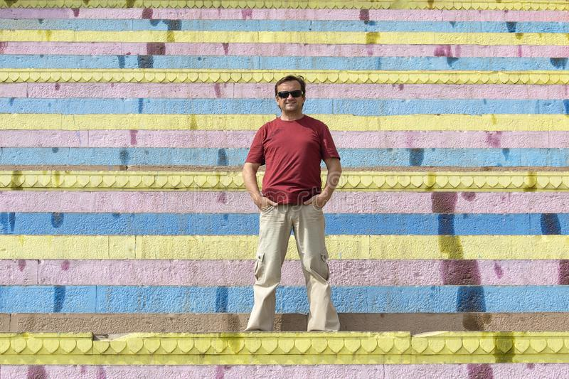 Middle-aged man stands on colorful stair in the city of Varanasi, India stock photography